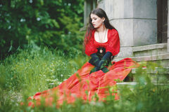 Woman in red Victorian dress. Sitting on stairs stock image