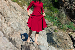 Woman in red walking on rocks Royalty Free Stock Image
