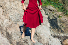 Woman in red walking on rocks Stock Photos