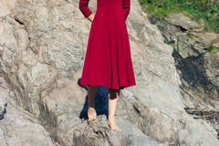 Woman in red walking on rocks Royalty Free Stock Photography