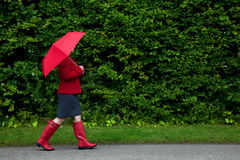 Woman in red walking with umbrella Royalty Free Stock Images