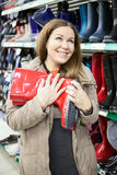 Woman with red waterproof shoes in hands buying in shop Stock Photography
