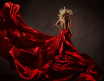 Woman in red waving dress with flying fabric. Back side view Stock Photography