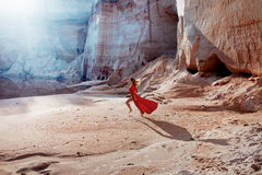 Woman in red waving dress with flying fabric runs Stock Image