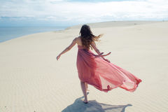 Woman in red waving dress with flying fabric runs on background of dunes. Back view Stock Photo