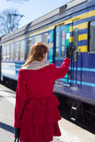 Woman in red waving hand on the platform Stock Photos