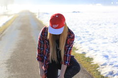 Woman in Red and White Cap and Red Blue and White Plaid Button Up Shirt and Black Denim Jeans on Gray Road during Daytime Stock Photo