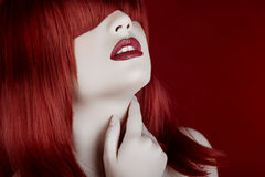 Woman with red wig and pale white doll look type skin. On red background in studio photo Stock Photo