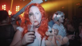 Woman in red wig and saw stuck in head dance with plushy bear at halloween party stock footage
