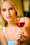 Woman with red wine. Portrait of young beautiful blond woman with red-wine glass, indoors Royalty Free Stock Photos