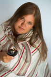 Woman with red wine glass. Blond young woman covered with a blanket, drinking red wine Royalty Free Stock Photo