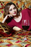 Woman with a red wine glass on a magnificent sofa Royalty Free Stock Photos