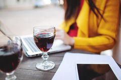 Woman with red wine tablet and laptop in street cafe Stock Photography