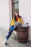 Woman with red wine tablet and laptop in street cafe Royalty Free Stock Image