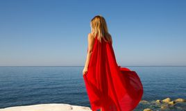 Woman in red. Woman in the red dress on the white stone at the beach in Cyprus Stock Image