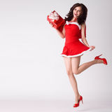 Woman in red xmas sexy costume jump with gift Stock Image
