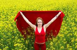 Woman in Red in Yellow Flowers. A beautiful young woman dressed in bright red standing in the middle of a field of yellow flowers royalty free stock images
