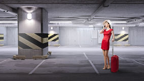 Woman in red. Young woman in red dress with red luggage talking on mobile phone Stock Images