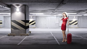 Woman in red. Young woman in red dress with red luggage talking on mobile phone Stock Photography