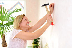 Woman redecorate home and working with hammer Royalty Free Stock Photos
