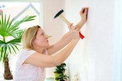 Woman redecorate home and working with hammer Royalty Free Stock Images