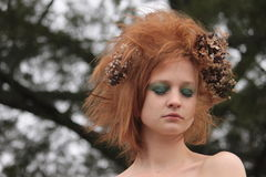 Woman with RedOrange Teased Hair with Dead Flowers. A woman with green eye make up and dead flowers in her hair Royalty Free Stock Images