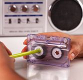 Woman reeling compact audio cassette with a pen royalty free stock photos