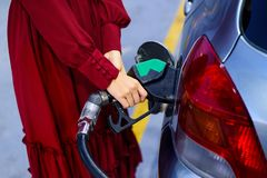 Woman adding petrol on gas station. Woman refiling petrol on gas station close up royalty free stock photography