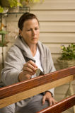 Woman Refinishing Piece of Furniture. A middle-aged woman refinishes a piece of furniture Stock Image
