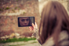Woman is reflected on the screen of her mobile phone Stock Image
