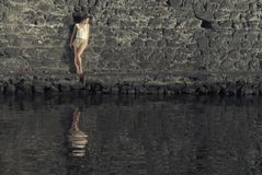 Woman reflection. Young woman against the wall with reflection in the water Stock Images