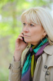 Woman reflective phoning. Senior woman reflective phoning outdoor Royalty Free Stock Image