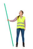 Woman In Reflective Vest Holding Chroma Key Rod And Watching. Young woman in yellow reflective vest, jeans, and lumberjack shirt standing legs apart, holding Royalty Free Stock Photography