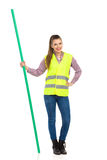 Woman In Reflective Vest Holding Chroma Key Stick. Young woman in yellow reflective vest, jeans, and lumberjack shirt posing with hand on hip and holding chroma Stock Photos
