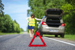 Woman in reflective vest near broken car. On the roadside. Focus on red triangle warning sign Stock Image