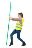 Woman In Reflective Vest Struggle With Chroma Key Rod. Young woman in yellow reflective vest, jeans, and lumberjack shirt posing with hand on hip and holding Stock Images