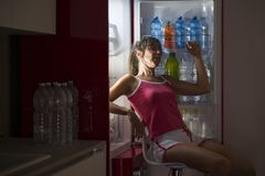 Woman refreshes herself sitting in front of the fridge Royalty Free Stock Images