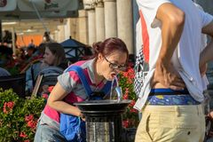 Woman is refreshing at fountain in sweltering hot days on Main Square in Cracow. Cracow, Poland - July 5, 2018: Woman is refreshing at fountain in sweltering hot royalty free stock photography