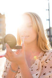 Woman refreshing makeup with gloss in the sun Stock Photo