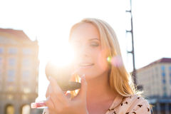 Woman refreshing makeup with gloss in the sun. Woman wears makeup with gloss or lipstick in the sun Royalty Free Stock Photography