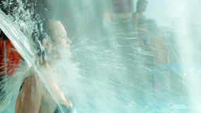 Woman refreshing under water shower in the pool. Young woman refreshing under strong water stream in the pool. View through the shower stock video footage