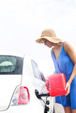 Woman refueling car against clear sky on sunny day Stock Photos