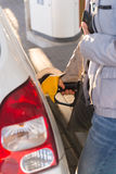 Woman refueling car tank and holding wallet Stock Image