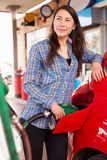 Woman refuelling a car at a petrol station Royalty Free Stock Photo