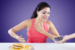 Woman refuse junk food and choose blueberry Royalty Free Stock Photography