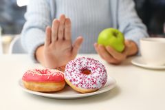 Woman refusing to eat donuts and choosing apple instead. Diabetes concept