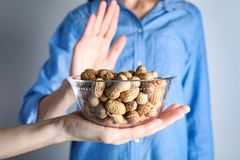 Woman refusing to eat peanuts. Food allergy concept