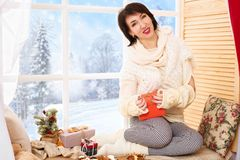 Woman with reg box gift is sitting on a window sill. Beautiful view outside the window - sunny day in winter forest and snow stock photos