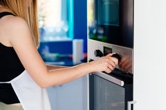 Woman regulates the temperature of the oven - 250C. royalty free stock image