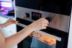 Woman regulates the time of the baking royalty free stock image